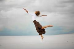 Junge Frau springt auf Sand in der Wüste und im frohen Lachen Lizenzfreies Stockbild