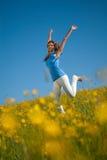 Junge Frau springt in eine Wiese Stockbilder