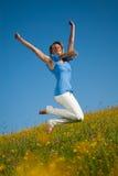 Junge Frau springt in eine Wiese Lizenzfreies Stockbild