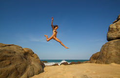 Junge Frau springt von den Felsen Lizenzfreies Stockfoto