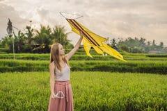 Junge Frau startet einen Drachen auf einem Reisgebiet in Ubud, Bali-Insel, Indonesien lizenzfreie stockfotografie