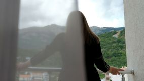 Junge Frau steht auf Balkon und schaut um grüne Berge voran stock footage