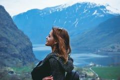 Junge Frau steht auf dem Hintergrund von schönen Bergen und von See Lizenzfreie Stockfotografie