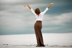 Junge Frau steht auf Sand in der Wüste Rückseitige Ansicht Lizenzfreie Stockfotos