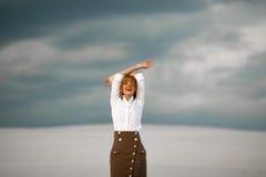 Junge Frau steht auf Sand in der Wüste und im frohen Lachen Stockbild