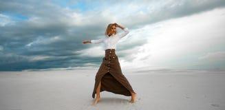 Junge Frau steht barfuß in der Wüste auf Himmelhintergrund Stockfotografie