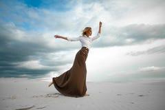 Junge Frau steht barfuß in der Wüste auf Himmelhintergrund Lizenzfreie Stockfotografie