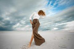 Junge Frau steht barfuß in der Wüste auf Himmelhintergrund Lizenzfreies Stockfoto