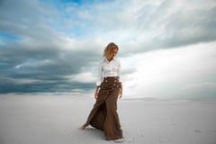Junge Frau steht barfuß in der Wüste auf Himmelhintergrund Stockbilder