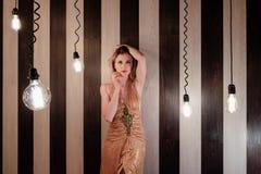 Junge Frau steht in der Dunkelkammer mit vielen leuchtenden Lampen lizenzfreies stockbild