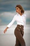 Junge Frau steht in der Wüste auf Himmelhintergrund Porträt Lizenzfreie Stockbilder