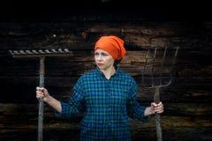 Junge Frau steht mit einer Heugabel nahe einem Stall auf einer Ranch lizenzfreie stockfotos