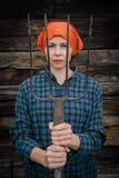 Junge Frau steht mit einer Heugabel nahe einem Stall auf einer Ranch lizenzfreies stockbild