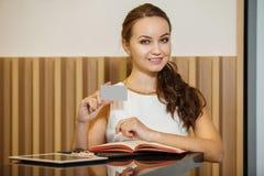 Junge Frau steht nahe Tabelle und hält Visitenkarte lizenzfreie stockfotografie