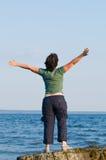 Junge Frau am Strand mit den Armen ausgestreckt Stockfotos