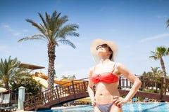 Junge Frau am Swimmingpool Stockfotografie