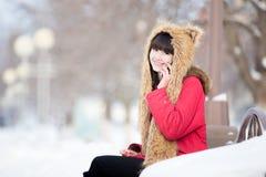 Junge Frau am Telefon auf der Bank draußen in der Winterzeit Stockfotografie