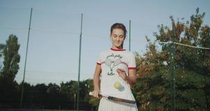 Junge Frau am Tennisplatz im Freien, Schläge der Tennisball vom Schläger in der Zeitlupe stock video footage