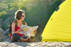Junge Frau touristisch nahe gelegen das Zelt, das Karte untersucht Lizenzfreie Stockfotos