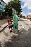 Junge Frau trägt Pappstatue von Liberty At Immigration P stockfotografie