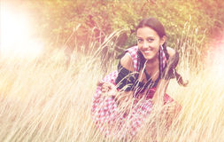 Junge Frau tragender Dirndl, der auf dem Gebiet aufwirft Lizenzfreie Stockfotografie