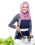 Junge Frau tragendes hijab, das Suppe machend für Abendessen sich vorbereitet Lizenzfreie Stockbilder