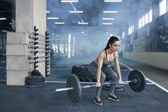 Junge Frau trainiert im gesunden Lebensstil der Turnhalle, der Barbellnahaufnahme hält Stockfoto