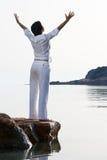 Junge Frau trifft den Sonnenaufgang, der barfuß auf bleibt Stockfoto