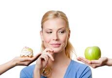 Junge Frau trifft eine Wahl zwischen Kuchen und Apfel Lizenzfreie Stockfotos