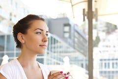 Junge Frau trinkendes coffe in einem Kaffee draußen Stockbilder