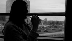 Junge Frau trinkt frisch zusammengedrückten Saft in einem Café und heraus schaut das Fenster auf dem Großstadthintergrund lizenzfreie stockfotografie