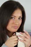 Junge Frau trinkt ihren Tee/Kaffee Stockfotografie