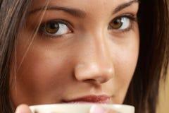 Junge Frau trinkt ihren Tee/Kaffee Lizenzfreie Stockfotografie