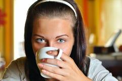 Junge Frau trinkt Kaffee Stockfotos