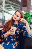 Junge Frau trinkt Kaffee im Einkaufszentrencaf? Latte haltenes und entspannendes M?dchen lizenzfreie stockfotografie