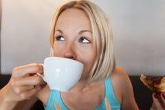 Junge Frau trinkt Morgenkaffee mit Hörnchen Lizenzfreie Stockfotografie