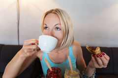 Junge Frau trinkt Morgenkaffee mit Hörnchen Stockbilder