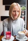 Junge Frau trinkt Morgenkaffee mit Hörnchen- und Lichtkremeisnachtisch Stockbild