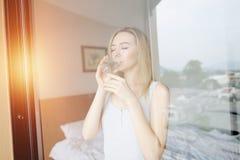 Junge Frau trinkt Wasser nach aufwachen mit Sonnenlicht auf dem Balkon stockbild