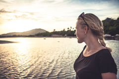 Junge Frau am tropischen Strand, der den Abstand während des schönen Sonnenuntergangs mit Kopienraum untersucht Stockbilder