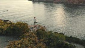 Junge Frau tun Yoga an der Sonnenuntergang-Antenne stock footage