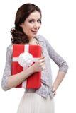Junge Frau umarmt ein Geschenk, das im roten Papier eingewickelt wird Stockfotografie