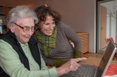 Junge Frau und ältere Frau mit Notizbuch stockbilder