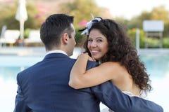 Junge Frau und Ehemann, die am Pool sitzt Stockfotografie
