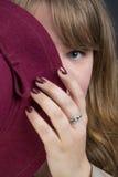 Junge Frau und ein purpurroter Hut Lizenzfreie Stockfotografie
