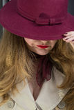 Junge Frau und ein purpurroter Hut Stockbilder