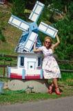Junge Frau und eine große Spielzeugbemehlenmühle Stockbild
