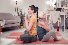 Junge Frau und eine Frau von mittlerem Alter, die zusammen Yoga tut stockfotos