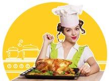Junge Frau und gebratenes Huhn in der Küche Stockfotografie