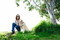 Junge Frau und goldener Apportierhund im Gras Stockfotografie